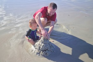 dad and son building a sand castle